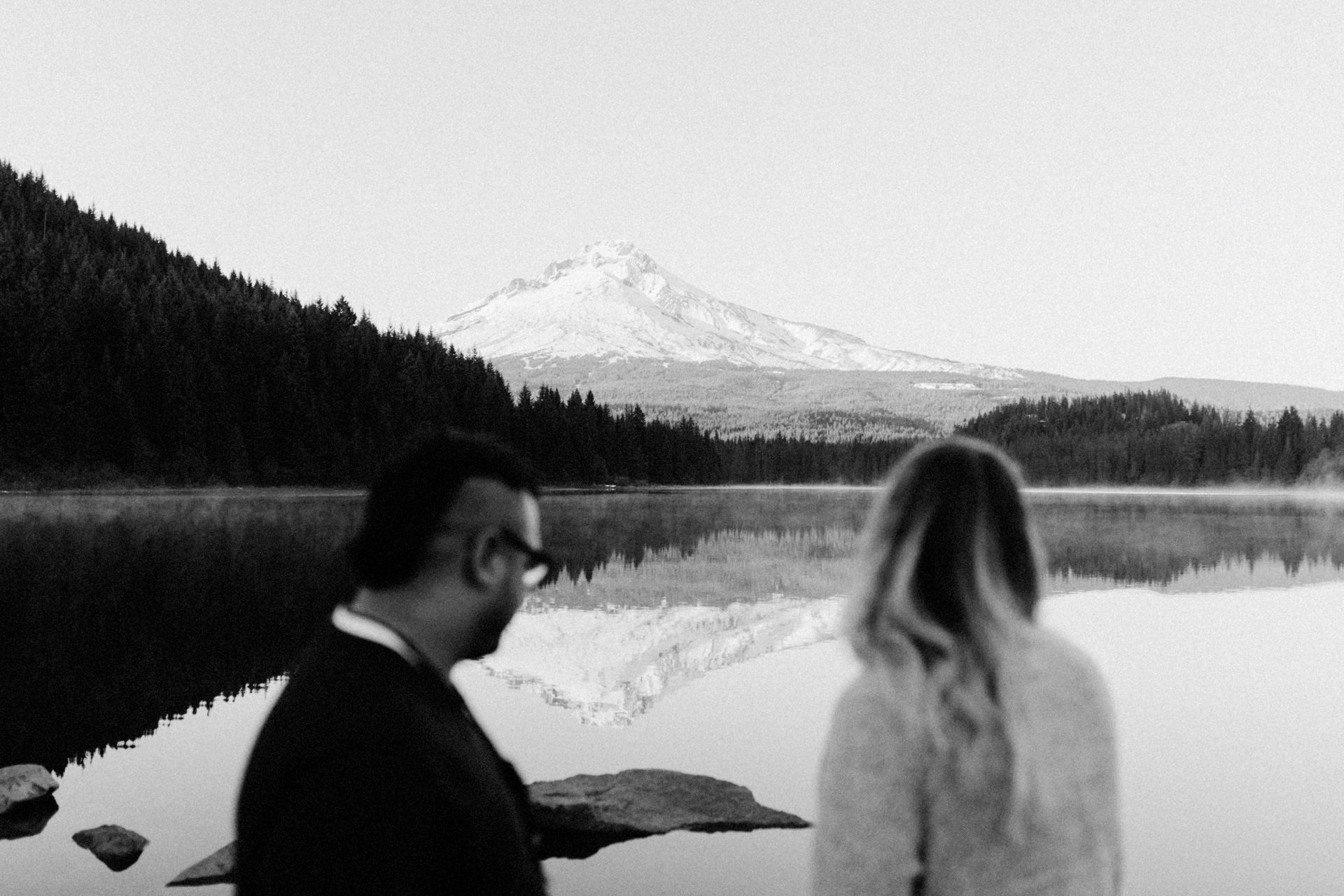 Mount hood and a couple looking out at the view of Trillium Lake