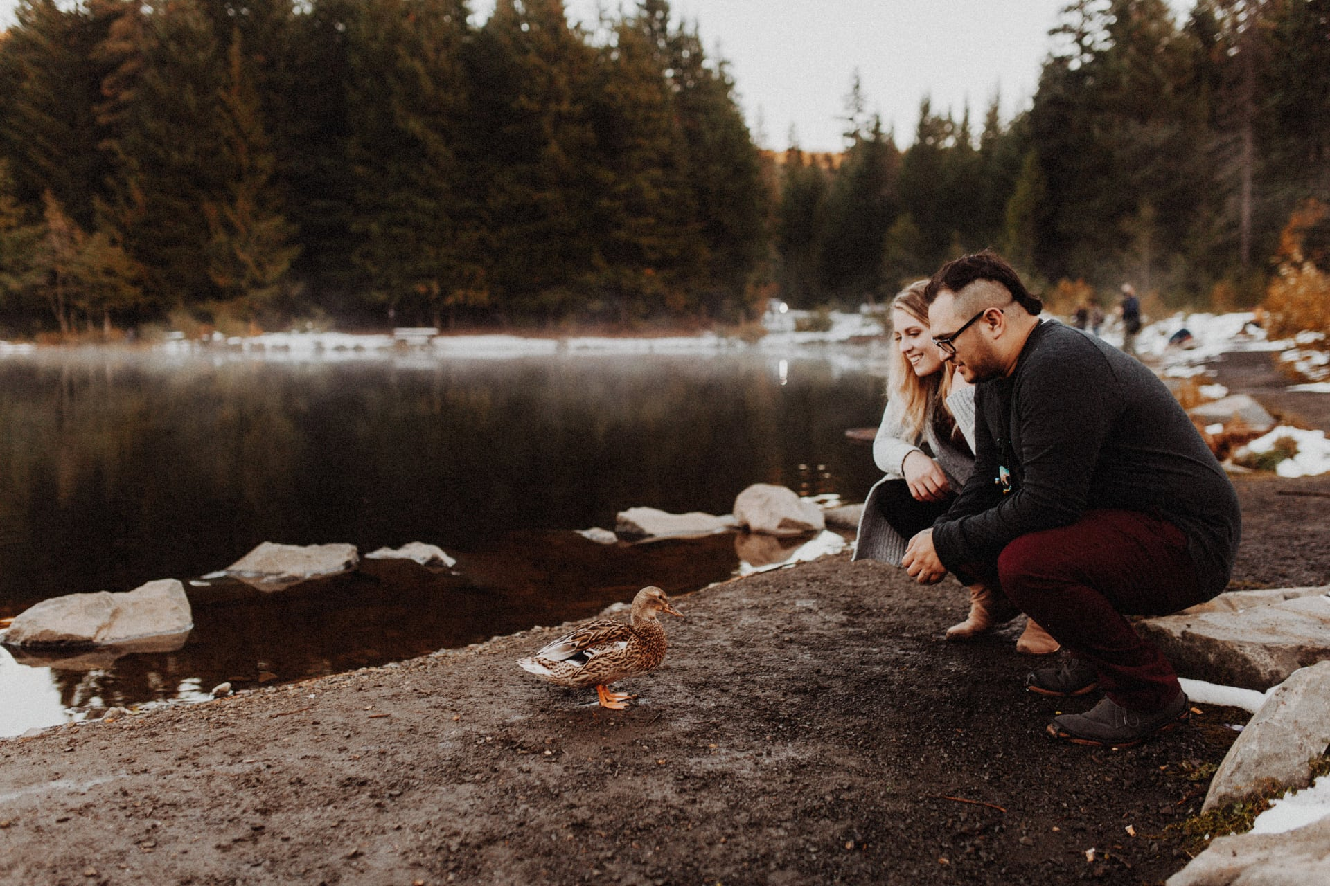 A man and woman feeding ducks at Trillium Lake