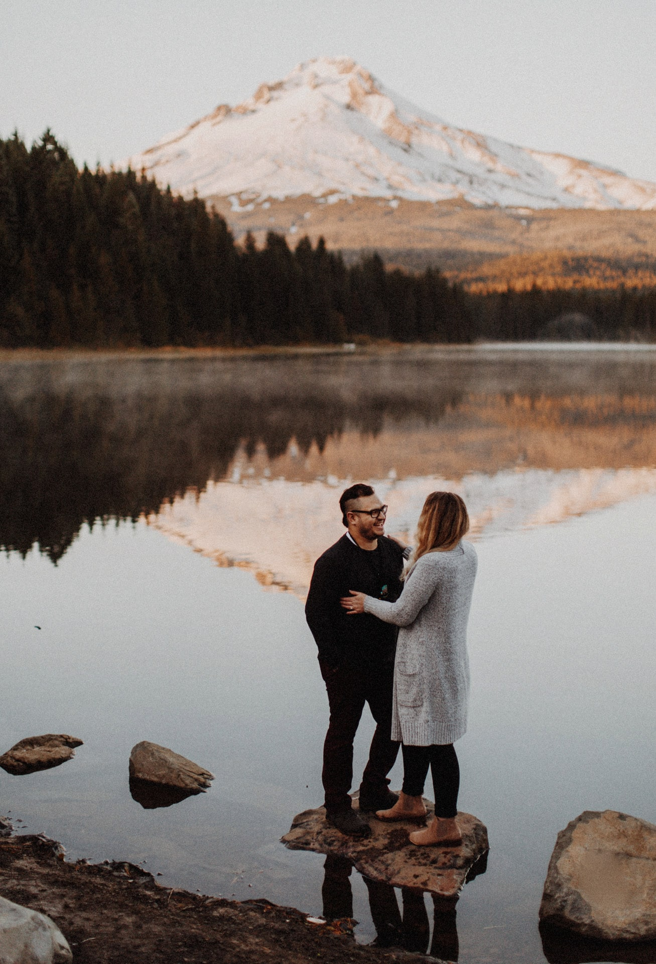 A Couple together in front of Trillium lake looking out at Mount hood