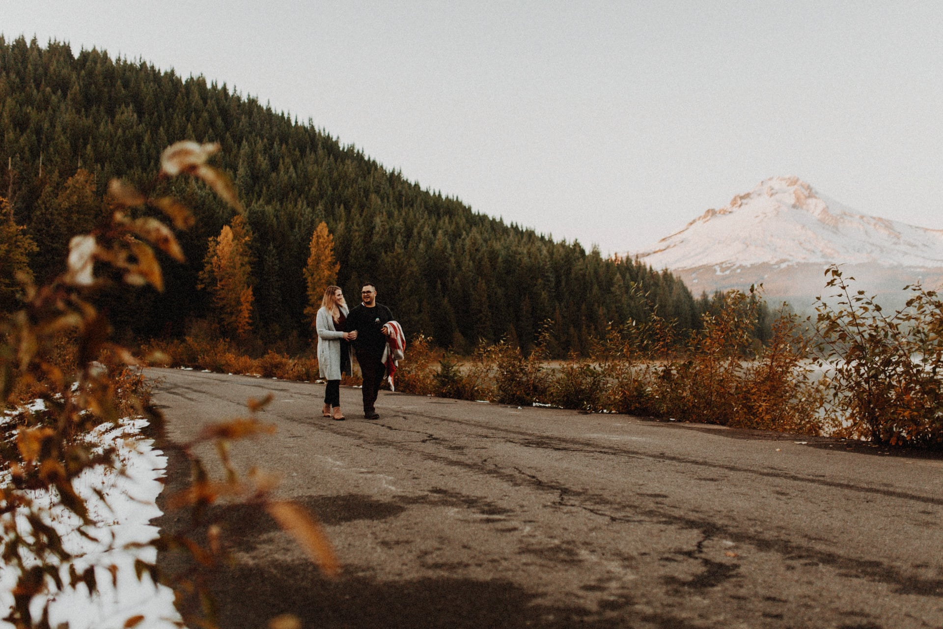 A couple walking down the road at trillium Lake in front of Mount Hood