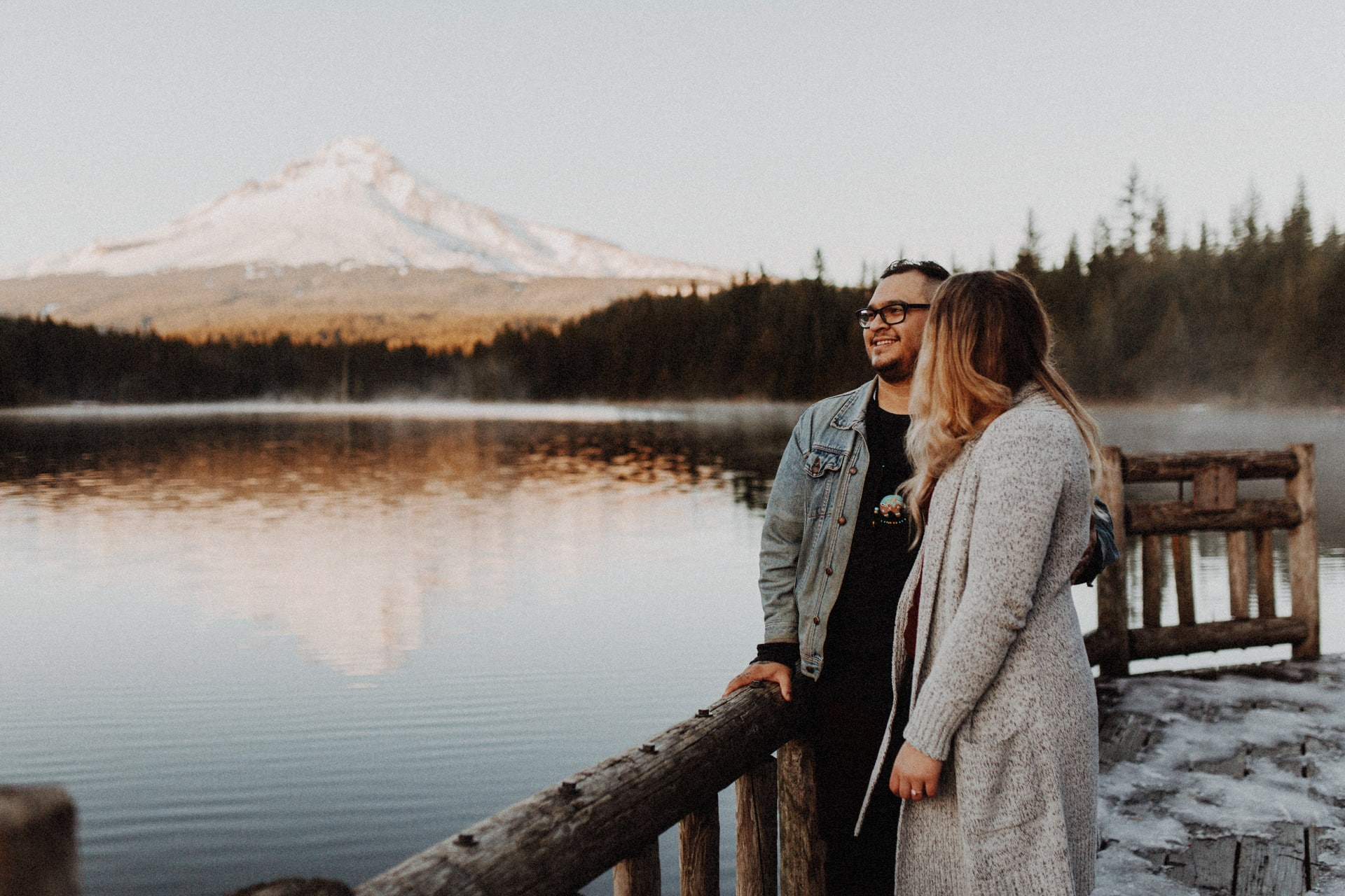 Couple standing on a dock at trillium lake in front of mount hood